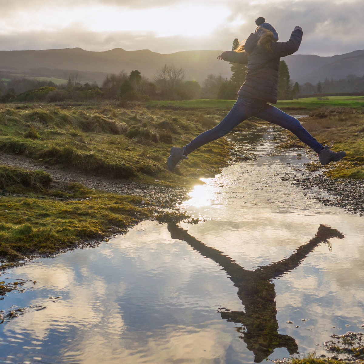 Girl in jacket and woolly hat jumping over stream