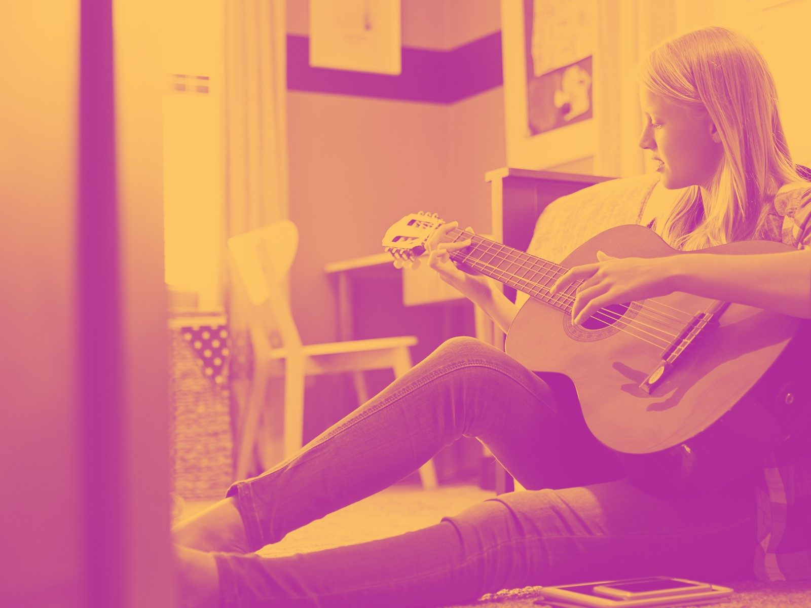 Girl playing guitar sitting on bedroom floor