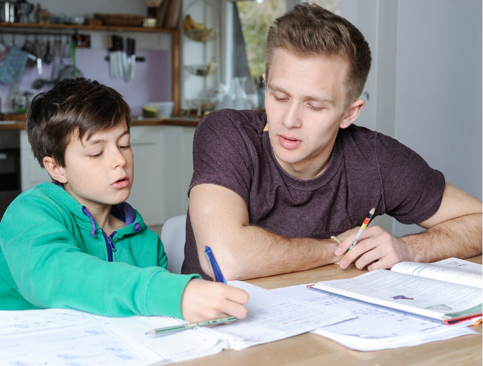 Young man helping younger male sibling with schoolwork