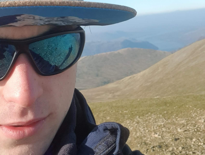 Guy hiking with sunglasses and a hat on