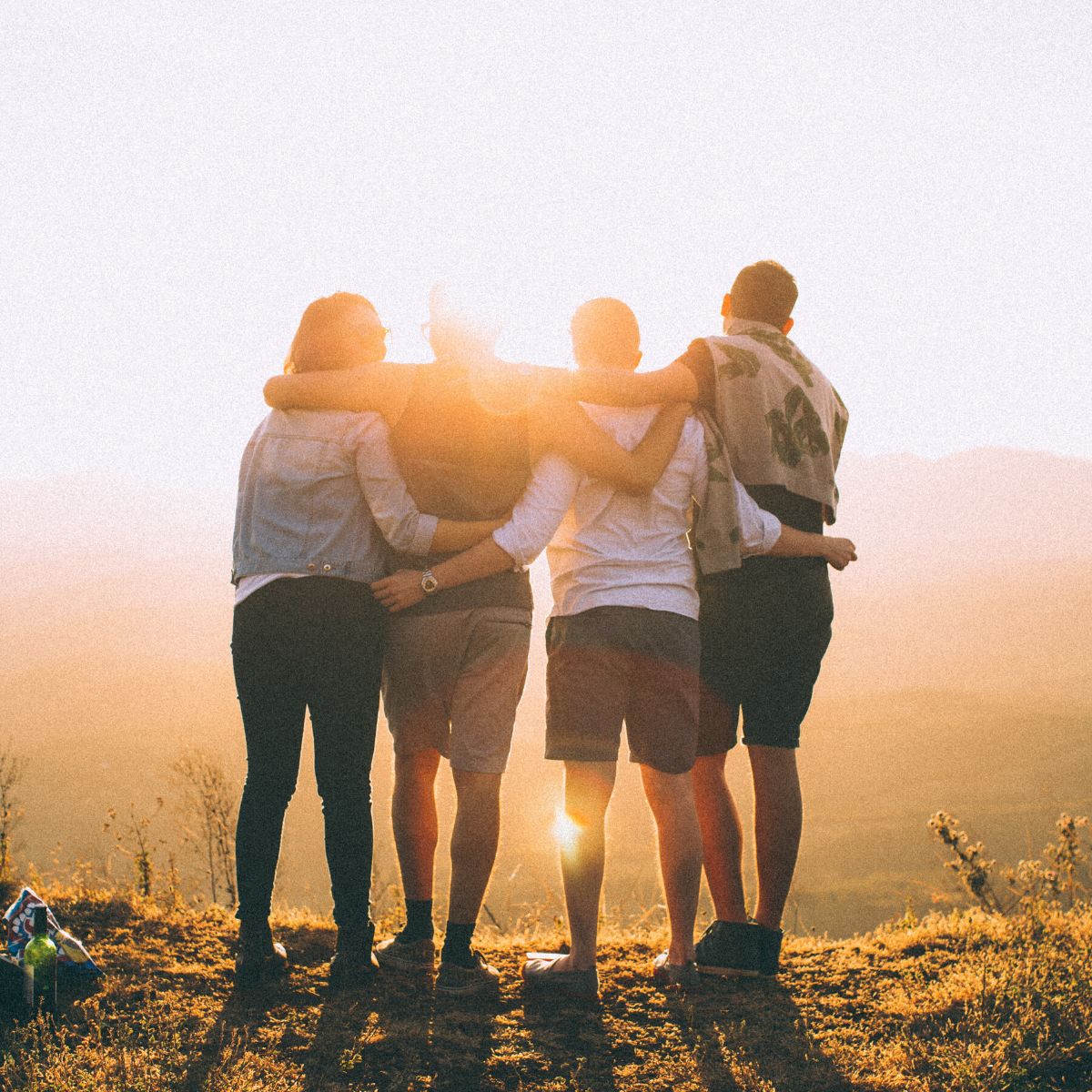 Group of young people hugging at sunset