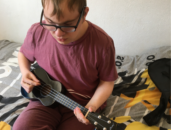 Young man playing ukulele in bedroom