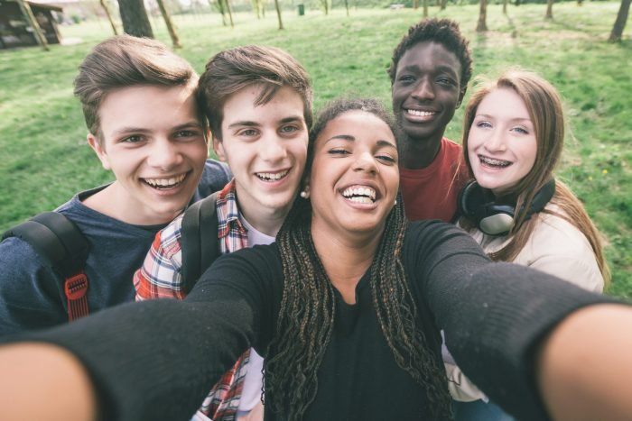 Group of young people smiling and taking a selfie