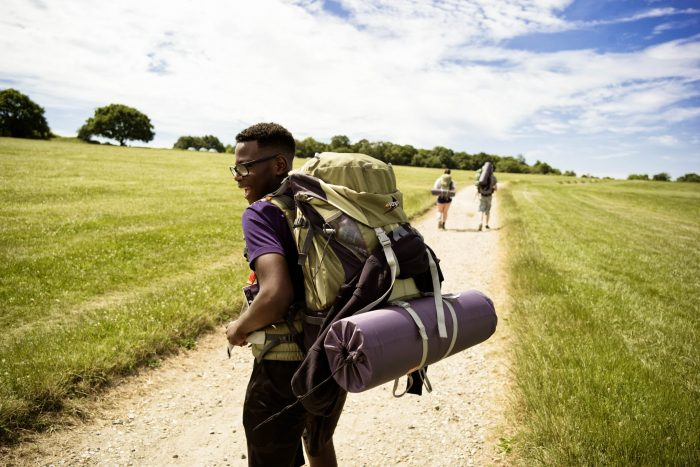 Young man on expedition wearing backpack