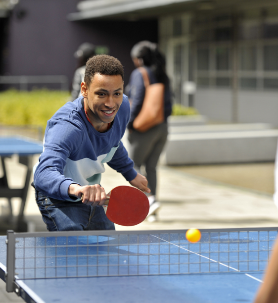 Young man playing table tennis at college