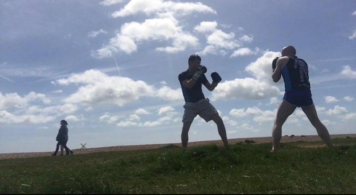 Two boxers practising in a field