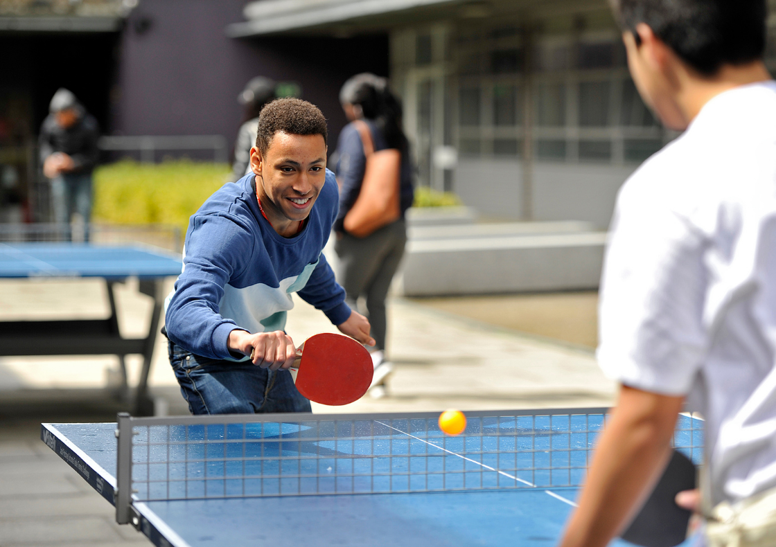 Young man playing ping pong in blue jumper