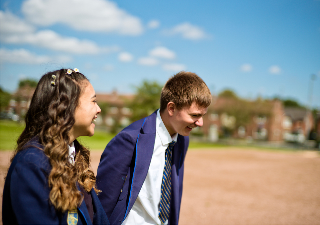 Male and female school pupils in uniform walking and laughin