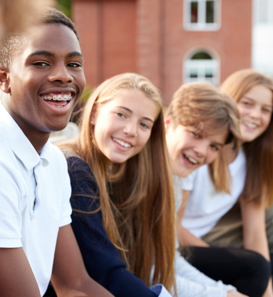 Group of young people sat on a wall smiling