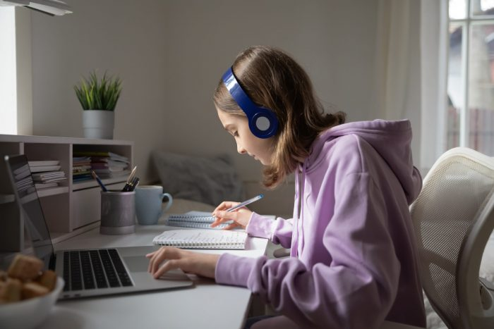 Young person in purple hoodie working at desk with laptop wearing headphones