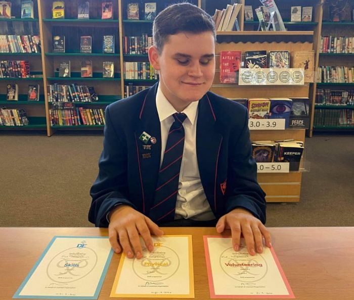 Fred a young man sitting in a library wearing school uniform