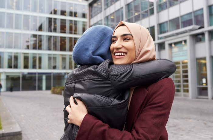 Two women in head scarves hugging in front of building and smiling