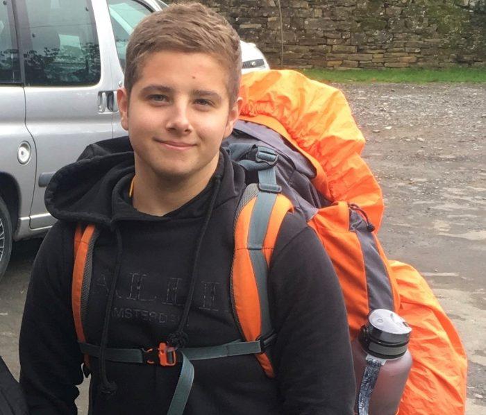 Joseph on expedition wearing orange backpack