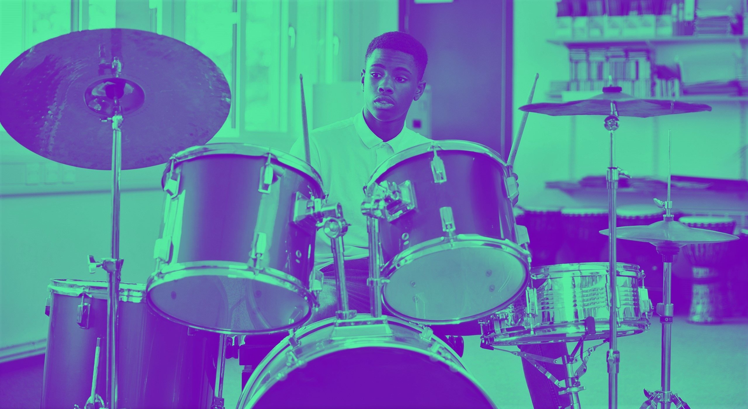 Young man learning to play drums in bedroom