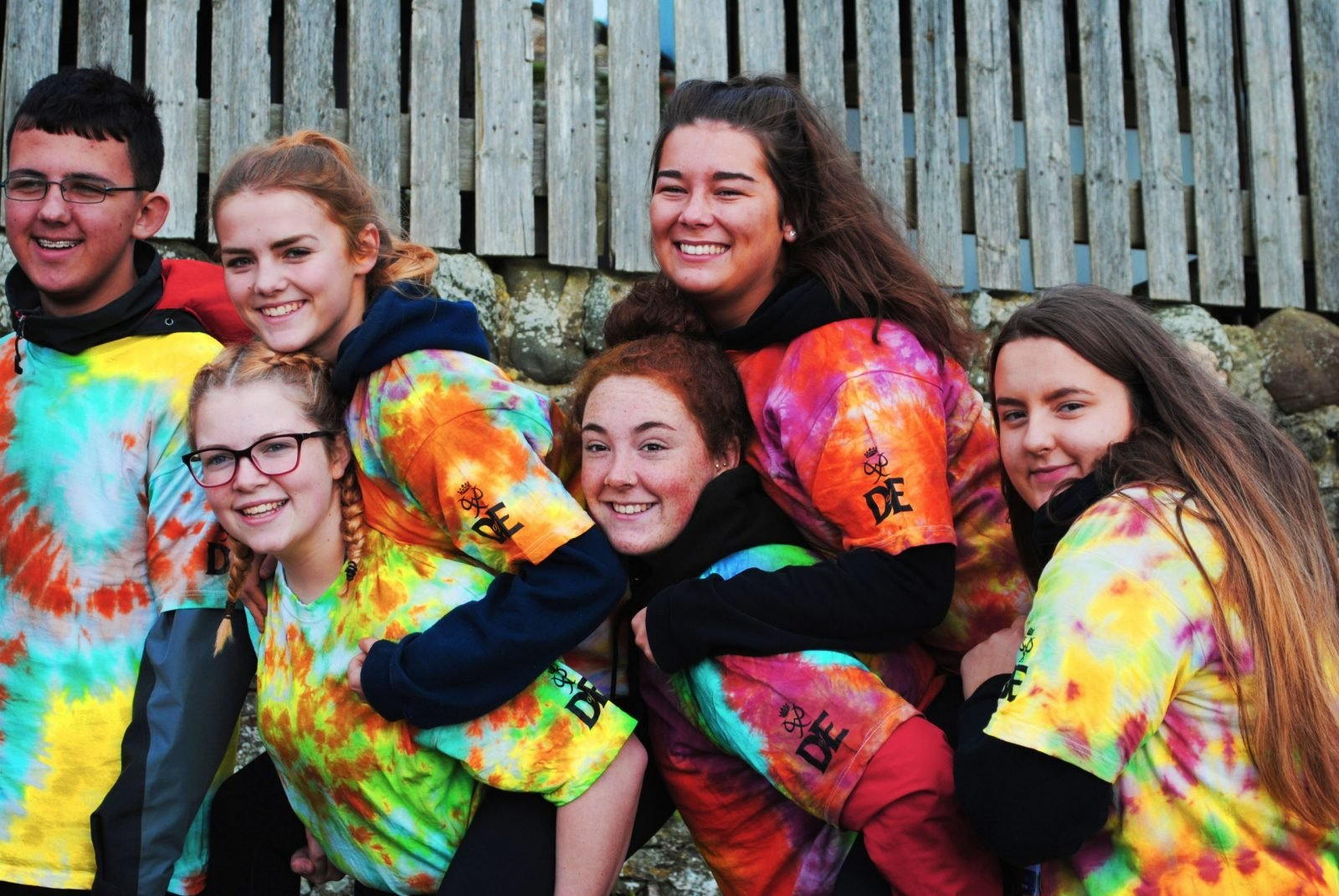 Group of smiling young people in multicoloured tshirts