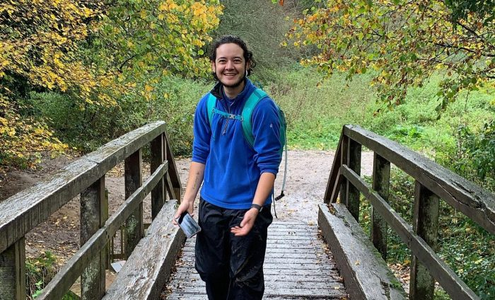Luke standing on wooden bridge wearing blue jumper