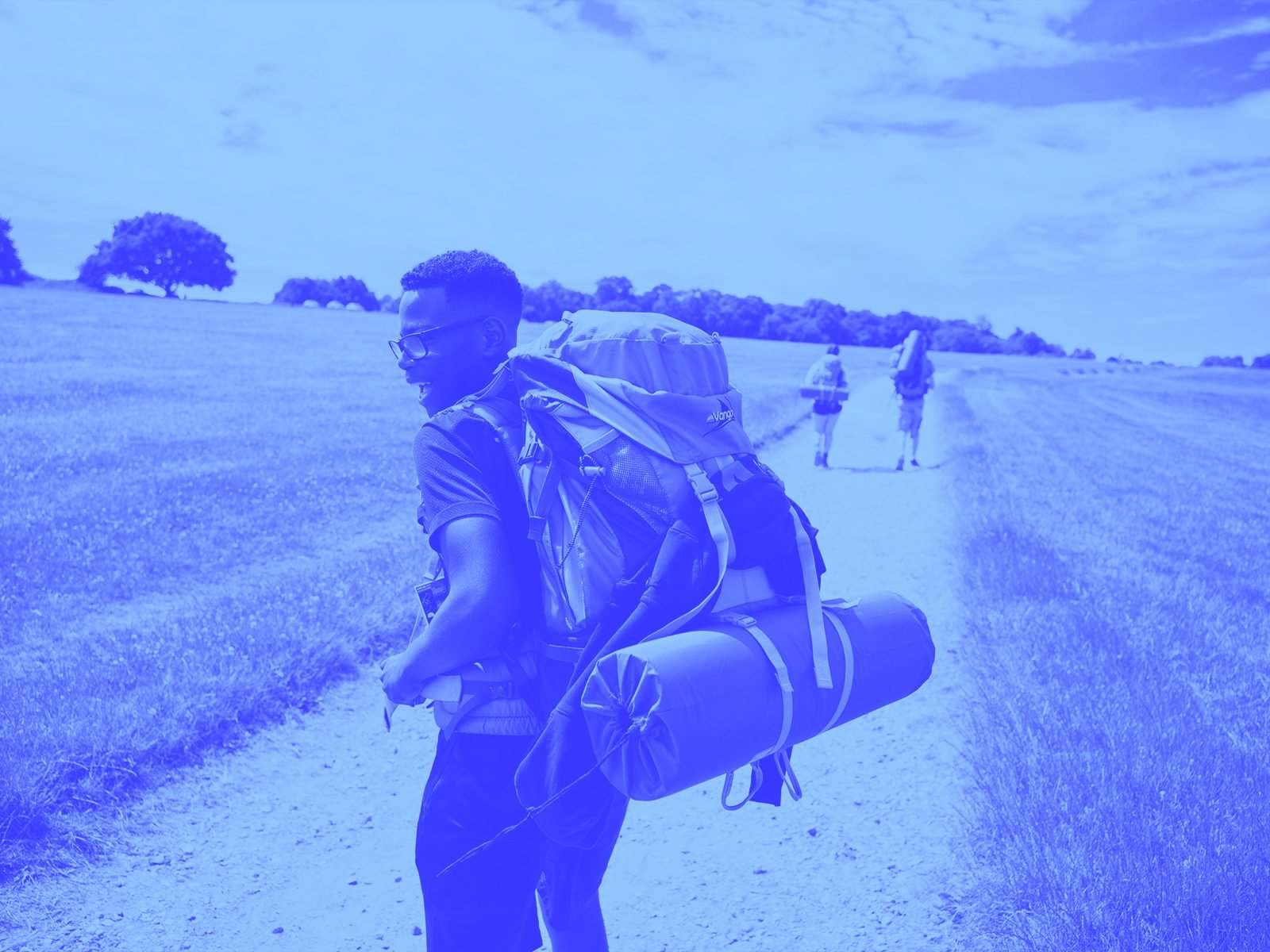 Young person on expedition wearing backpack - blue duotone