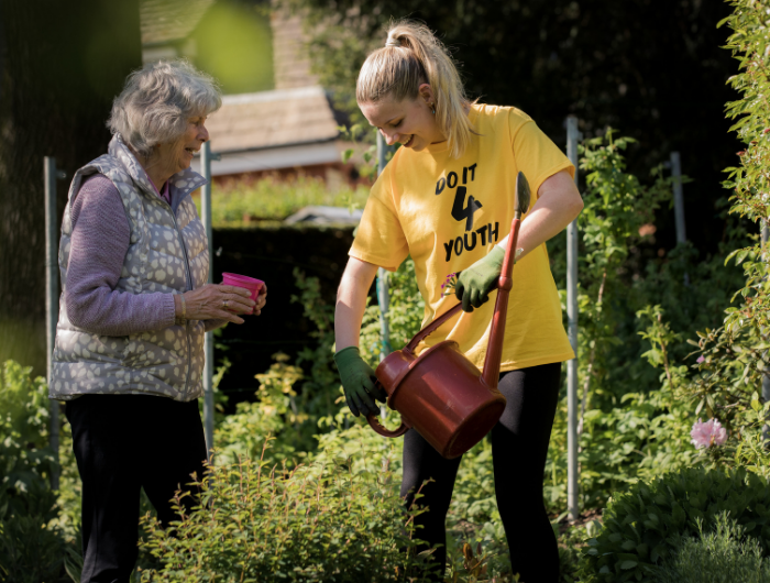 Young woman helping elderly woman with gardening