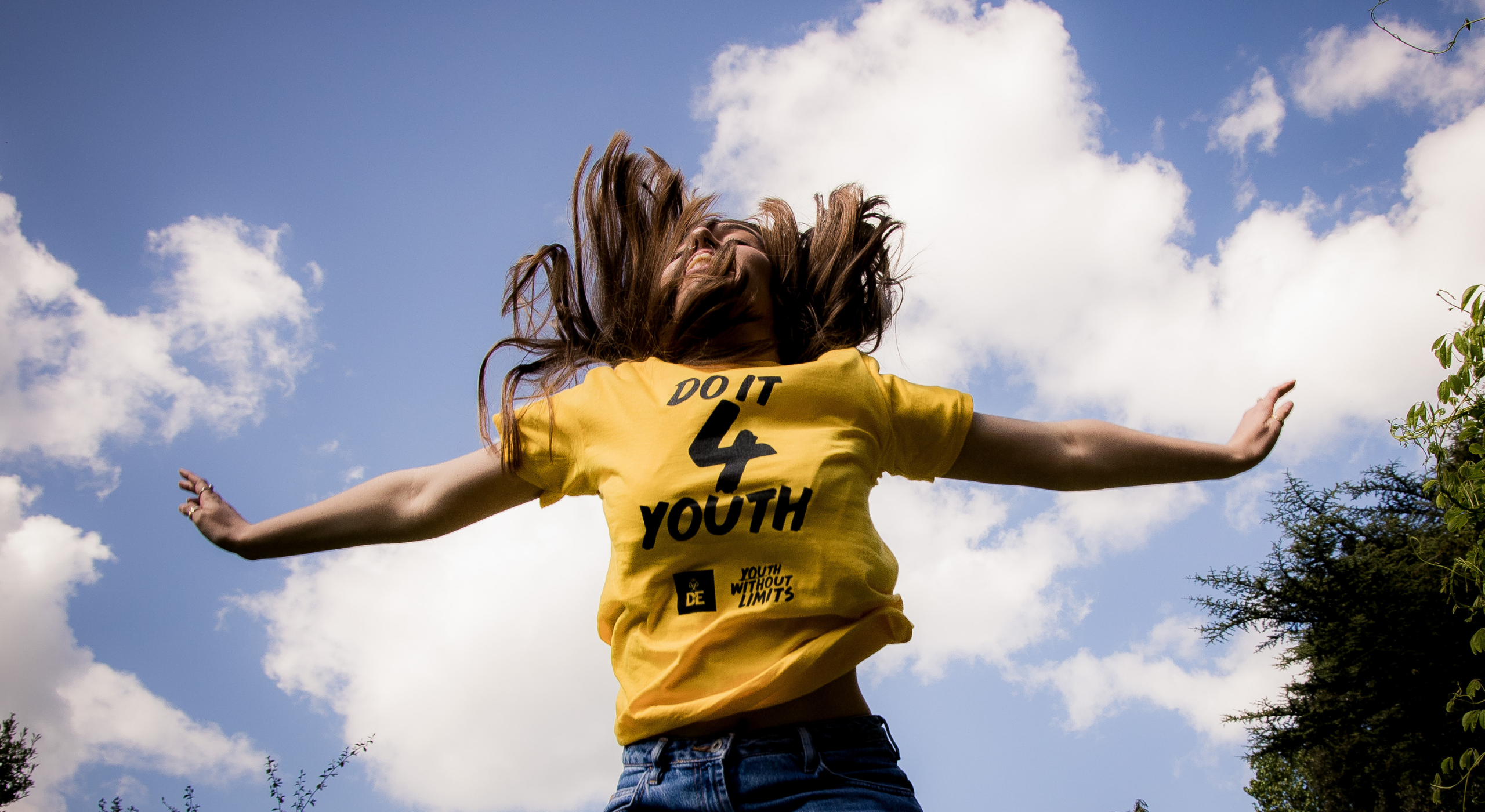 Happy person jumping in yellow Do It 4 Youth t-shirt