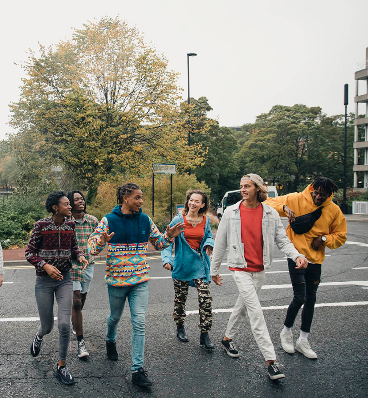 Group of happy and diverse young people walking on the street