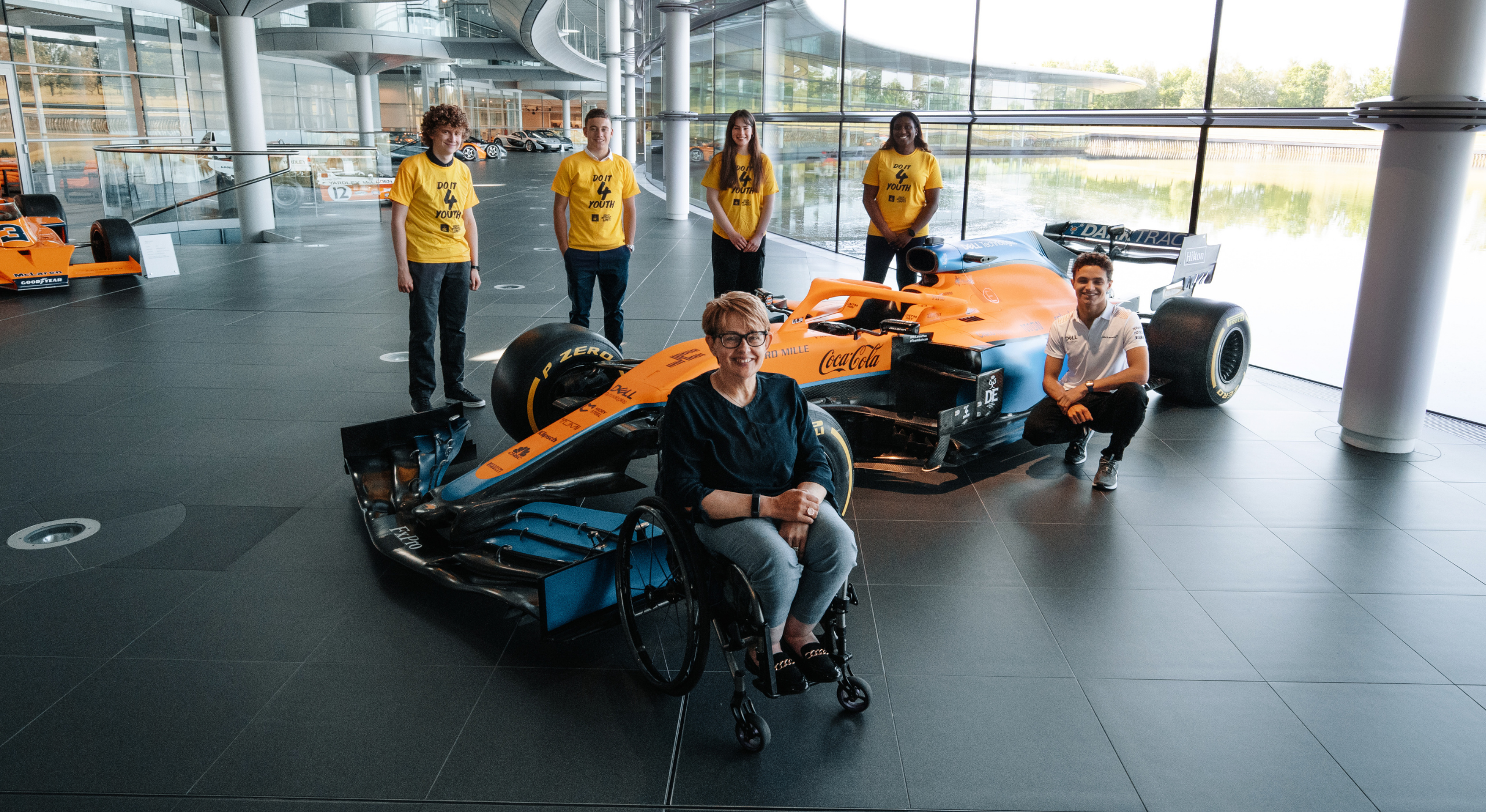 Group of Do It 4 youth participants with lando norris with a McClaren racing car